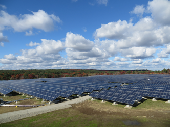 Picture of solar arrays on the Clay Pit Road site. The foreground is grass and the background is blue sky and clouds.